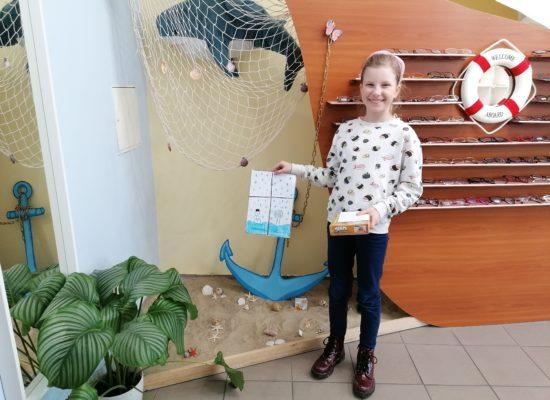 Zuzanna ze swoją pracą konkursową oraz nagrodę. W tle statek z oprawkami optomi, kotwica, zielona roślinka